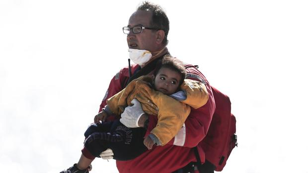 Red Cross volunteer Stavros Zembillis carries a child from a cargo ship loaded with migrants which has arrived in Crete (AP)