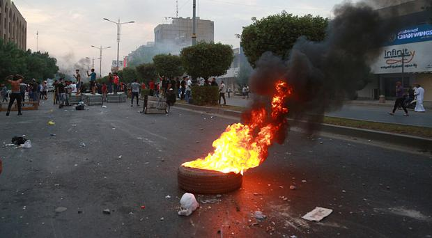 Protesters block a street and burn tyres during a demonstration in Baghdad (Hadi Mizban/AP)