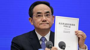Xu Lin, vice head of the publicity department of the Communist Party shows a copy of the white paper on fighting Covid-19 (Andy Wong/AP)