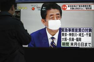 A pedestrian stops to watch a TV news report as Shinzo Abe declares a state of emergency (Eugene Hoshiko/AP)