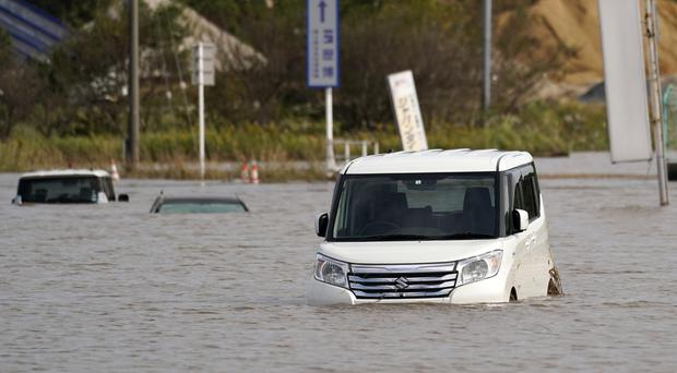 Vehicles are submerged in floodwaters after torrential rain in Sakura city, Chiba prefecture (Kyodo News via AP)
