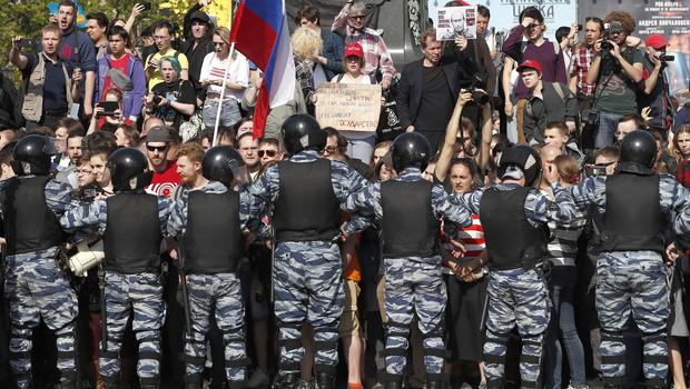 Russian police push protesters back during a demonstration in Pushkin Square in Moscow (Pavel Golovkin/AP)
