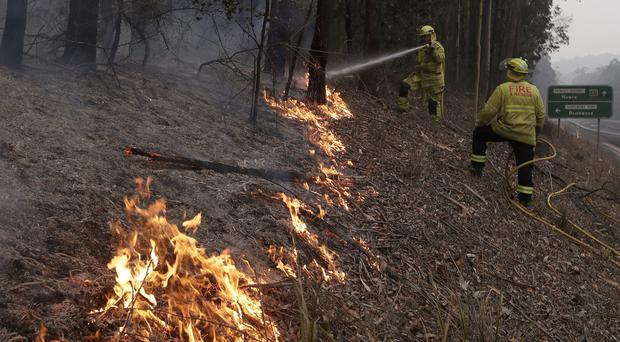 Firefighters manage a controlled burn to help contain a larger fire near Falls Creek, Australia (Rick Rycroft/AP)
