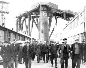 Harland & Wolff shipyard workers finish for the day as the massive Sea Quest dominates the skyline in 1966
