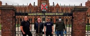 Members of Lasair Dhearg outside Queen's University with their 'replacement sign'