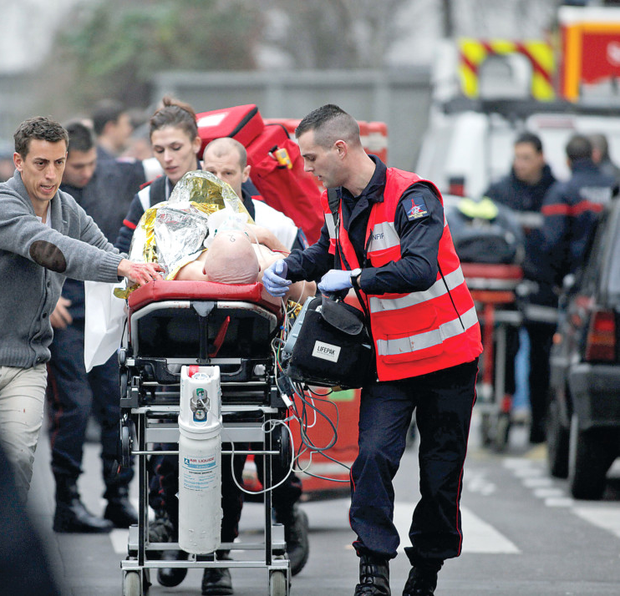 An injured person is taken to an ambulance after this week's terror attack at the French satirical newspaper Charlie Hebdo's office in Paris