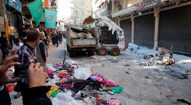 Lebanese workers clear debris from the site of a twin bombing attack in Beirut which killed 44 people last week