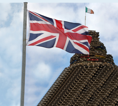A Union flag with an Irish tricolour on a bonfire in the background