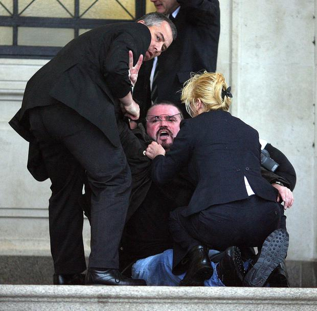 Stone being apprehended by security at Stormont