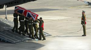 Soldiers carry the Union flag-draped coffin of Lance Corporal Chris Harkett from an aircraft at RAF Lyneham in Wiltshire after he was killed in Helmand in Afghanistan with two of his Army comrades