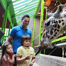 Killian McCandless (6), his sister Emily (5) and their father Peter feed the giraffes at Belfast Zoo