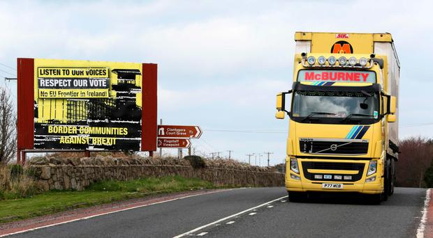 A lorry passes poster for campaign group Border Communities Against Brexit in Co Armagh
