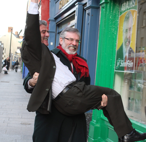 Gerry Adams carries Arthur Morgan over the threshold at the official opening of Sinn Fein election campaign office in Drogheda