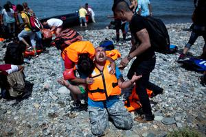 A refugee from Syria prays after arriving on the shores of the Greek island of Lesbos aboard an inflatable dinghy across the Aegean Sea from from Turkey
