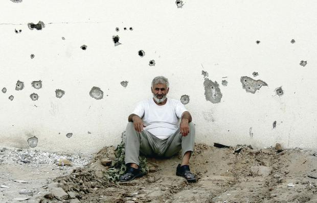 War wounds: a Palestinian leans against the damaged wall of a building in Gaza City's Shijaiyah