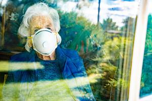 Uncertain times: a care home resident gazes thoughtfully through the window