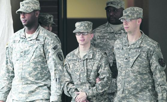 Army man: Bradley Manning — flanked by military police — released thousands of documents to Julian Assange of WikiLeaks