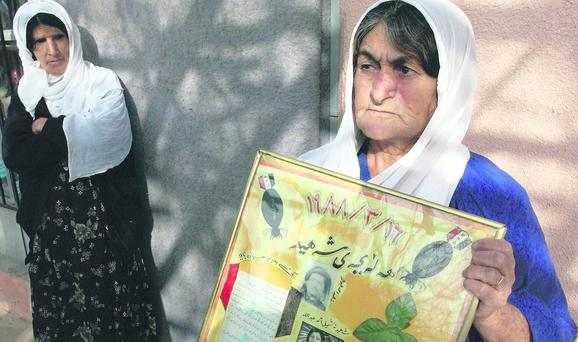 In mourning: women hold posters after Saddam Hussein's chemical bombing of civilians in Halabja in 1988