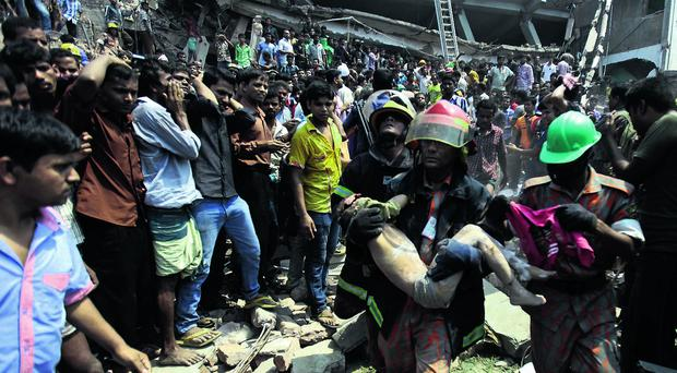 Tragedy: A child is pulled from the rubble at the Dhaka factory