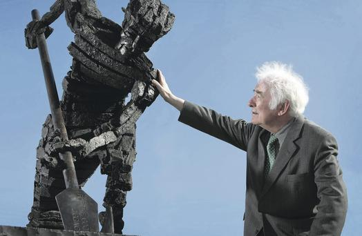 Tribute: Seamus Heaney places his hand on the sculpture of his father digging peat which was unveiled in his native Bellaghy in 2009