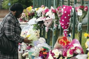 LONDON, ENGLAND - MAY 24:  A member of the community lays flowers close to the scene where Drummer Lee Rigby of the 2nd Battalion the Royal Regiment of Fusiliers was killed, on May 24, 2013 in London, England. Drummer Lee Rigby of the 2nd Battalion the Royal Regiment of Fusiliers was murdered by suspected Islamists near London's Woolwich Army Barracks. The UK's security services are facing a Commons inquiry after confirmation that the two men arrested were known to MI5.  (Photo by Dan Kitwood/Getty Images)