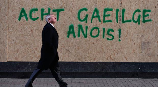 A man walks past graffiti which calls for an Irish Language Act
