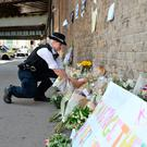 A Met Police officer lays flowers given by a member of the public close to Finsbury Park Mosque