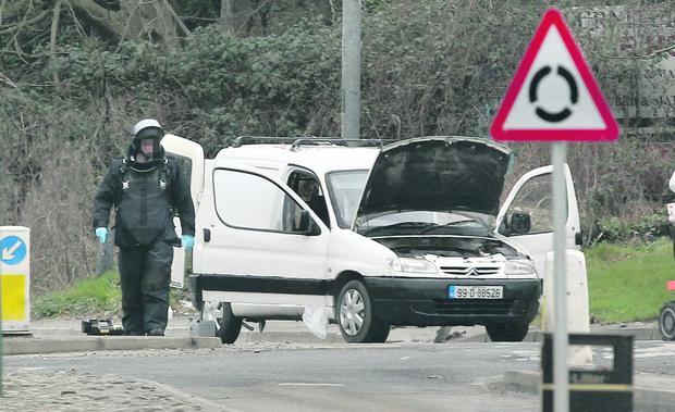 Probe: a bomb-disposal expert examines the mortar van in Derry