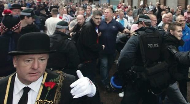 Orangemen, protesters and police remonstrate during a parade in Donegall Street