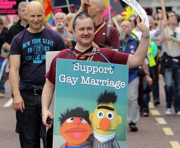 Gay Pride parade in Belfast in 2012 with marcher carrying a placard featuring Sesame Street's Bert and Ernie