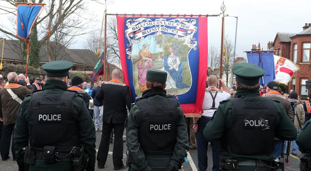 A line of police meets Orange Order protesters near Twaddell Avenue in north Belfast. The Orange Order hopes for a resolution to the stand-off before July