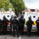 Riot police form a protective line as protesters gather ahead of the Twelfth parade at Woodvale Road, north Belfast, on Monday