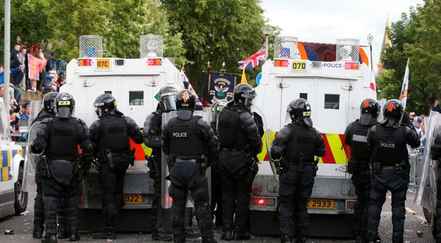 Riot police form a protective line as protesters gather ahead of the Twelfth parade at Woodvale Road, north Belfast, on Monday, 13 July.