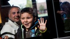 A boy refugee smiles on a bus taking migrants to a short-term housing facility in Berlin, Germany. Germany is welcoming thousands of refugees while the UK considers them a nuisance