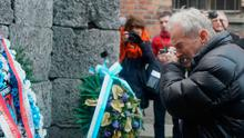 A man weeping at the execution wall in the former Auschwitz concentration camp on Monday