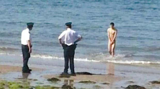 Officers apprehend a naked man on the shoreline