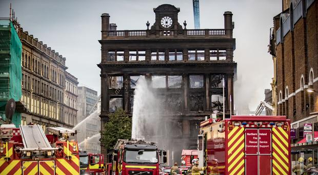 Firefighters work to put out the blaze at the Primark store in Belfast on Tuesday
