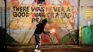 Riots: a youth throws a fire bomb over a peace wall