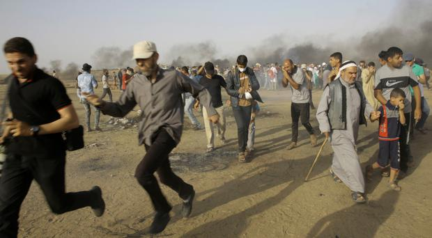 Palestinian protesters run for cover from teargas fired by Israeli forces near Gaza border