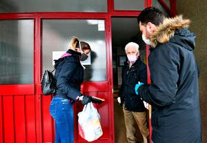 Volunteers in Bosnia deliver food to an elderly person during the lockdown
