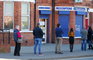 People practise social distancing as they queue at a chemist on the Ormeau Road in south Belfast