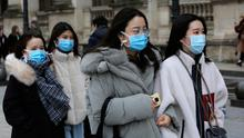 Tourists wearing masks walk past the Louvre museum in Paris