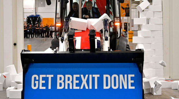 """Prime Minister Boris Johnson drives a Union flag-themed JCB, with the words """"Get Brexit Done"""" inside the digger bucket, through a fake wall emblazoned with the word 'gridlock', during a general election campaign event"""