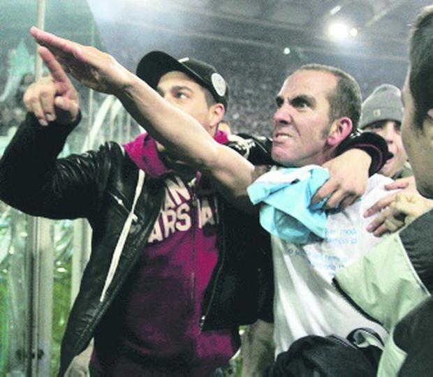 "Rome, ITALY: POUR ILLUSTRER LE PAPIER : "" Les groupes d'Ultras, entre extremisme et haine des ""flics"" "" - Picture taken 06 January 2005 of Lazio's forward Paolo Di Canio gesturing towards Lazio fans at the end of Lazio vs AS Roma Serie A football match at Rome's Olympic stadium. Lazio captain Paolo Di Canio is to be investigated by the Italian football federation (FIGC) over an alleged fascist salute during his side's 3-1 victory over bitter city rivals AS Roma. AFP PHOTO/Paolo COCCO (Photo credit should read PAOLO COCCO/AFP/Getty Images)"