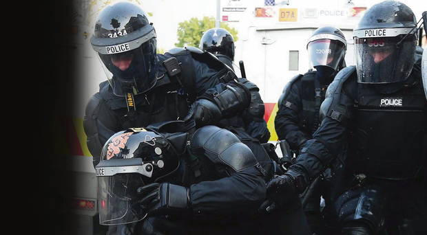 Feeling the heat: An injured police officer is helped by colleagues during summer rioting in Belfast, when the PSNI came under sustained attack from protesters
