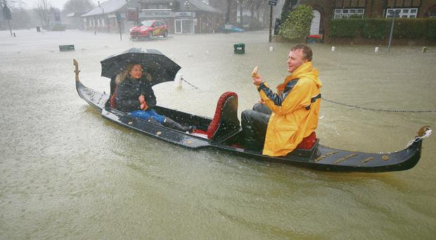 Raging planet: A couple promote their Italian restaurant by rowing their gondola through flood waters in Datchet, England