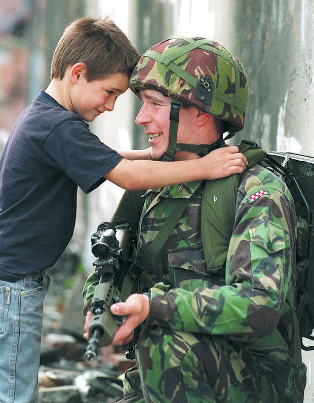 A symbol of hope as a soldier talks to a child on the Springfield Road in west Belfast