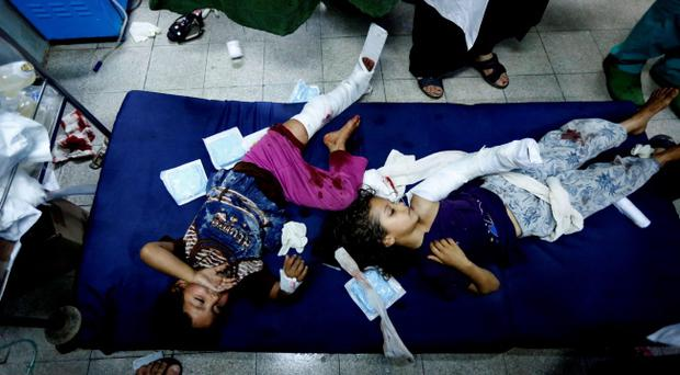 Palestinian children, wounded in an Israeli strike on a compound housing a U.N. school in Beit Hanoun, in the northern Gaza Strip, lay on the floor of an emergency room at the Kamal Adwan hospital in Beit Lahiya, Thursday, July 24, 2014. (AP Photo/Lefteris Pitarakis)