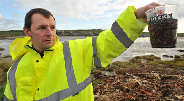 Ian holds up dirty rubbish retrieved from the coast