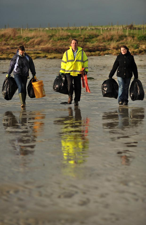 Dr Ian Humphries carries off the litter collected at a beach near St John's Point